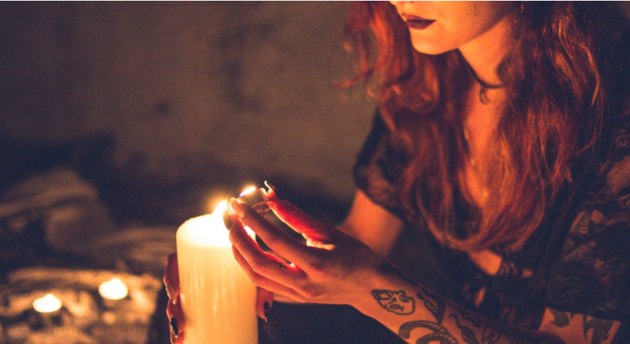 a witchy looking woman with tattoos in a circle with a candle